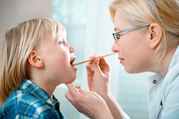 врач ищет симптомы охриплости голоса в горле у ребенка